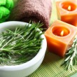 Branches of rosemary and sea salt in bowl, towels, candles and bottle with massage oil on wooden background. Rosemary spa concept — Stock Photo #64746795