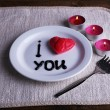 Cookie in form of heart on plate with inscription I Love You, and candles on napkin and wooden table background — Stock Photo #64748283