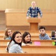 Group of students sitting in classroom and listening teacher — Stock Photo #64799395