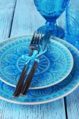 Empty colorful plate, glasses and silverware set on wooden table — Stock Photo