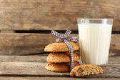 Tasty cookies and glass of milk on rustic wooden background — Zdjęcie stockowe