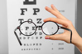 Glasses in hands on eye chart — Stock Photo