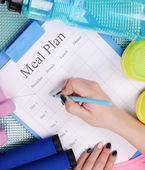 Meal plan and sports equipment — Stock Photo