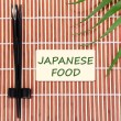 Pair of chopsticks and Japanese Food text on brown bamboo mat background — Stock Photo #64812763