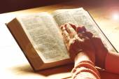 Hands of old woman with Bible on table, close-up — Stock Photo