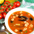 Tasty soup with mussels, tomatoes and black olives in bowl on wooden background — Stock Photo #64938955