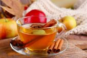 Composition of  apple cider with cinnamon sticks, fresh apples, warm scarf and autumn leaves on wooden background — Stok fotoğraf