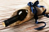 Wine bottle wrapped in burlap cloth on wooden planks background — Zdjęcie stockowe