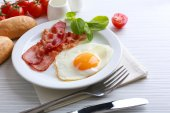 Bacon and eggs on color wooden table background — Stock Photo