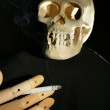 Human scull and wooden hand with cigarette on dark background — Stock Photo #64943643