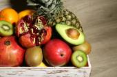 Assortment of exotic fruits in box on wooden background — Stock Photo