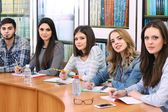 Group of students sitting at table in library — Foto Stock