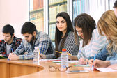 Group of students sitting at table in library — Stockfoto