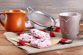 Pink cookies and cup of coffee on wooden table — Stock Photo