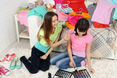 Two girls with clothes and decorative cosmetics at home — Stock Photo