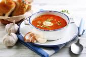 Ukrainian beetroot soup - borscht, on blue napkin, on wooden background — Stock Photo