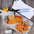 Breaded fried fish fillet and potatoes with sliced lemon and cutlery on cutting board and wooden planks background — Stock Photo #65015957
