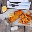 Breaded fried fish fillet and potatoes with sliced lemon and cutlery on cutting board and wooden planks background — Stock Photo #65015961