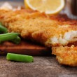 Breaded fried fish fillet and potatoes with asparagus and lemon on cutting board and rustic wooden background — Stock Photo #65015985