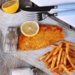 Breaded fried fish fillet and potatoes with sliced lemon and cutlery on cutting board and wooden planks background — Stock Photo #65015991