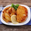 Breaded fried fish fillet and potatoes with asparagus and lemon on plate and wooden planks background — Stock Photo #65016041