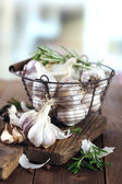 Raw garlic and spices on wooden table — Stock Photo