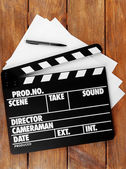 Movie clapper with sheets of paper and pen on wooden planks background — Foto de Stock