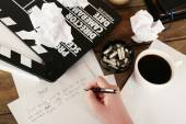 Female hand writing script at desktop with moving clapper and sheets of paper background — Stok fotoğraf