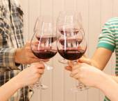 Clinking glasses of red wine — Stock Photo