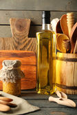 Wooden kitchen utensils with glass bottle of olive oil on wooden planks background — Stock Photo