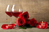 Composition with red wine in glasses, red roses and decorative heart on wooden background — Stockfoto