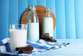 Glass and bottles of milk with chocolate chunks on stripped napkin and color wooden planks background — Stock fotografie