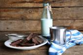 Metal mug and glass bottle of milk with chocolate chunks and strainer of cocoa on plate and rustic wooden planks background — Stock Photo