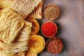 Different dry instant noodles with spices on wooden background — Stock Photo