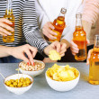 Friends hands with bottles of beer and snacks, close up — Stock Photo #65021161