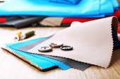 Colorful fabric samples with buttons and threads on wooden table background — Stock Photo
