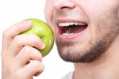 Man biting fresh green apple with healthy teeth isolated on white background — Stock Photo