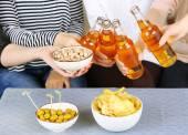 Vrienden handen met flessen bier en snacks, close-up — Stockfoto