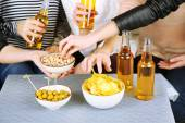 Friends hands with bottles of beer and snacks, close up — Stock Photo