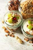Healthy layered dessert with muesli and fruits on table — Stok fotoğraf