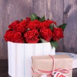 Bouquet of red roses in textile box with present on wooden background — Stock Photo #65125353