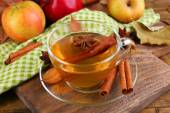 Composition of  apple cider with cinnamon sticks, fresh apples and autumn leaves on wooden background — Stock Photo