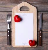 Cutting board with menu sheet of paper and hearts on rustic wooden planks background — Stok fotoğraf