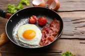 Bacon and eggs on rustic wooden planks background — Stock Photo