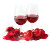 Composition with red wine in glasses, red roses, ribbon and decorative hearts isolated on white — Stock Photo