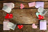 Heart shaped teabag tags on wooden background — Stock Photo