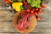 Raw beef steak on cutting board with vegetables and spices on wooden background — Stock Photo