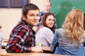 Group of students sitting in classroom and  listening teacher — Stock Photo
