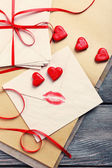 Love letters with red ribbon on wooden background — Stockfoto