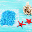 Sea salt crystals with sea shells, star fish  on color wooden background — Stock Photo #65339289